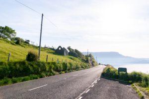 gray asphalt road between green grass field under white sky during daytime